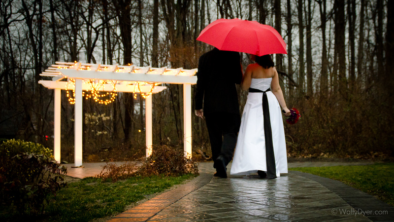 Rain during your wedding? Not even a problem. Here's a beautiful bride and groom in the rain with a red umbrella.